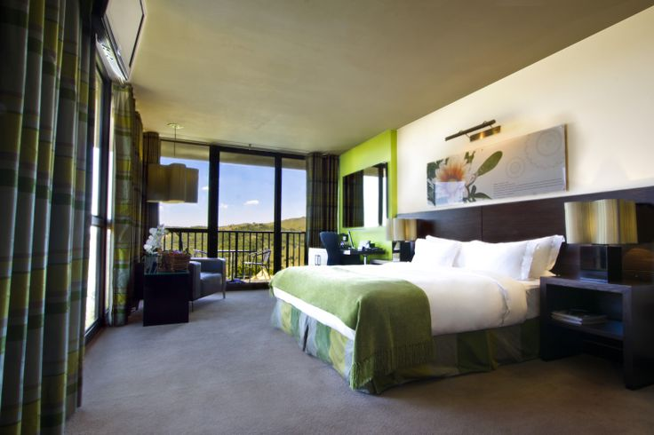 Luxury Bedroom - Green: These suites have large floor to ceiling windows overlooking the rolling landscape of the Klipriviersberg; they are located in the bush area of Thaba Ya Batswana ensuring quiet privacy. Each air-conditioned suite is equipped with large screen LCD television, and iPod docking station