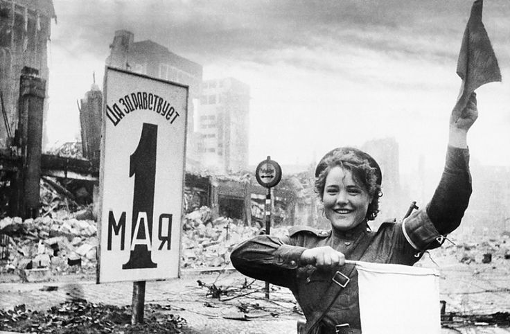 Berlin, May Day 1945. A smiling military policewoman, Maria Shalnova, directs traffic in the ruined streets.