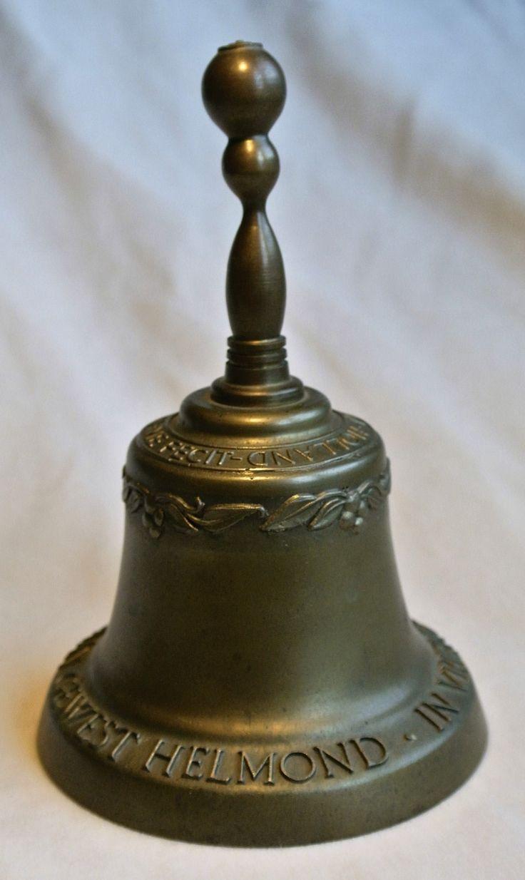 22 Handbel Eijsbouts  Nederland Ø 9,8 cm  15 cm hoog. Heel mooi gegoten bronzen handbel met een sierrand van blaadjes telkens vier druiven. Op de onderrand staat de tekst: IN VRIENDSCHAP STREEKORGAAN GEWEST HELMOND. Op de schouder staat; EIJSBOUTS ASTEN-HOLLAND-ME FECIT