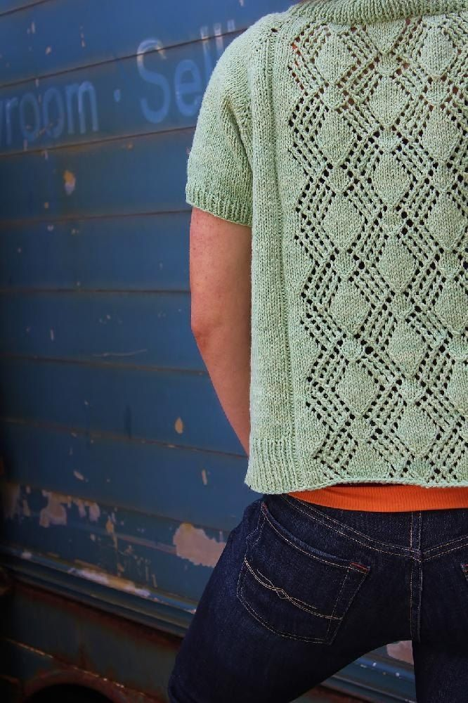 """Margarita is an easy, toss-on cardigan for summer. Bold lace on the back is echoed in the lace detail that finishes the ribbed collar. A casual length and short sleeves make this perfect over a sundress or shorts. The fit is open, with narrow front panels meant to showcase what's underneath, but directions are included to make the fit more traditional if you prefer a more closed silhouette. Choose the size that gives you about 2"""" of negative ease, based on bust size, for the fit shown. S..."""
