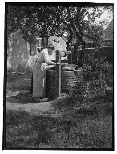 Het buurtschap Ooijman bij Doetinchem De tuin van een boerderij in de buurt van Doetinchem (het buurtschap Ooijman). Een vrouw haalt water uit een put. Naast de put staat een (was)mand. 1919 Collectie Stadsarchief Amsterdam #Gelderland #Achterhoek