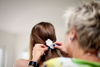 er wordt een bloem in het haar van de bruid gedaan