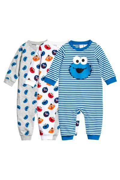 Pijamas, pack de 3: Pijamas em jersey macio de algodão com punhos e remate das pernas em malha elástica. Dois pijamas são estampados com botões de pressão na frente e ao longo de uma perna. Um pijama é às riscas com motivo estampado na frente e botões de pressão num ombro e no entrepernas.