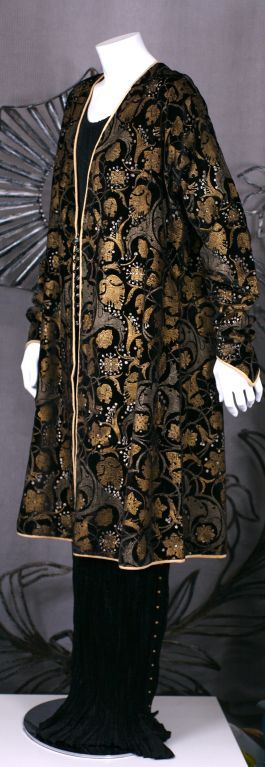 Mariano Fortuny Black Stencilled Velvet Persian Style CoatThis three-quarter length black velvet persian coat was printed with metallic paints with Venetian glass buttons and silk loop closures at the center front.    The hand stenciling is done with real gold metallic pigments aged to a mellow, burnished color. Fortuny built his stenciled pieces layer upon layer, until he achieved the effect of an old brocade.