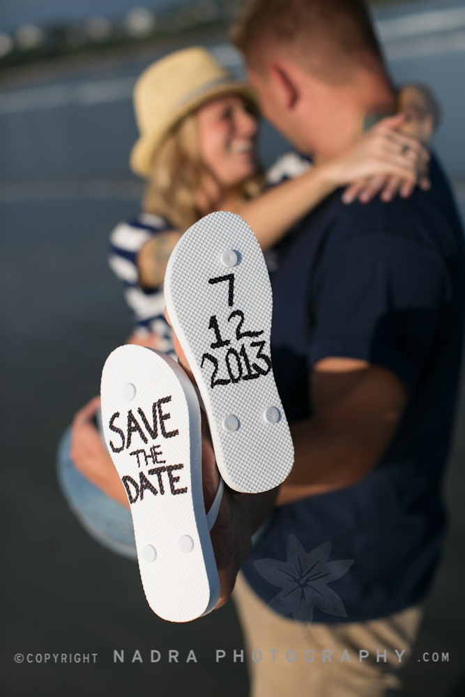 Save-The-Date!  Technical: 1. Daylight shot using natural light. 2. Shallow depth of field focuses on the announcement. 3. Angle of sandals hides any flaws in both subject's bodies Aesthetic:  4. Smiling bride helps portray the happy upcoming event 5. Golden hour suggests the warmth of love 6. White sandals for a white wedding 7. Message: Announcement 8. Great Beach lovers Engagement Announcement