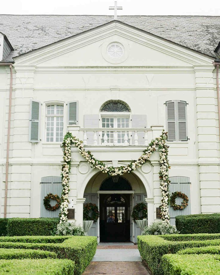 An Epic New Orleans Wedding with Classic Touches | Martha Stewart Weddings - A garland of hydrangea, roses, and limonium hung over the entrance to the Old Ursuline Convent, where the reception was held. Magnolia foliage wreathes dotted the French Colonial façade. Dating to 1752, it is the oldest building in the Mississippi Valley.