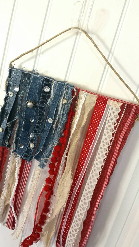 Shes a grand ole flag!! Add some rustic beauty and a touch of patriotic to your home decor with this unique fabric and ribbon scrap flag. Each piece is unique....no two flags are alike!! Made with ribbon and fabric lengths of monochrome reds, whites, and blues....then, adorned with mis-matched buttons and sequins to add the effect of stars. Flag dimensions are 12x18 and it comes with a jute cord hanger for easy display! Betsy Ross is a true artisan and seamstress....my version of Old Glory…