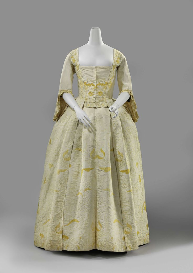 Robe à la francaise, France, 1740-1745. Cream-colored silk embroidered in yellow with slender, widely covered flowers and vines, blue linen lining.