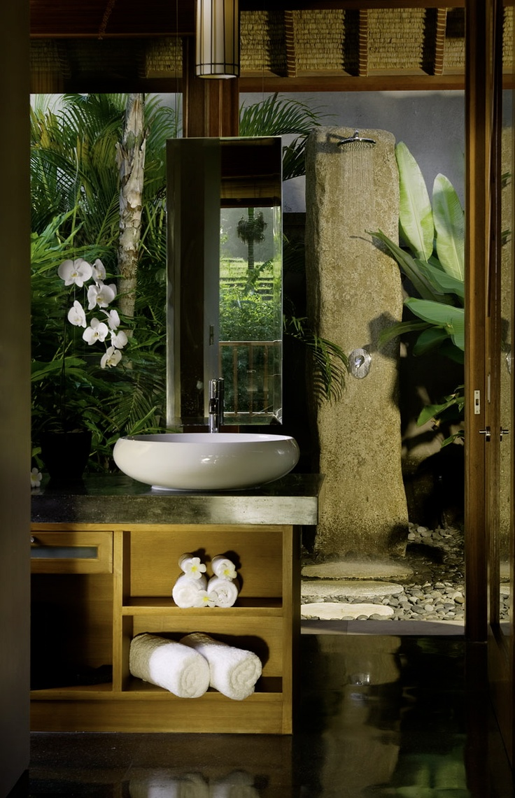 Balinese bathroom featuring a white round sink, wooden furniture and a nature inspired rain shower. Let the water wash over you while you inhale the beauty of the rice fields surrounding this villa | Pure Villa Lawana