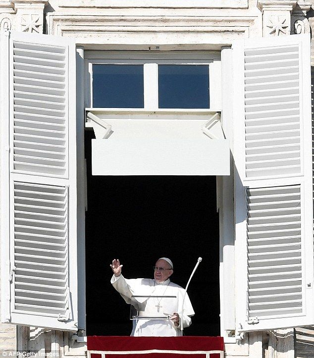 Pope Francis waves to the crowd from the window of the apostolic palace overlooking St.Peter's square