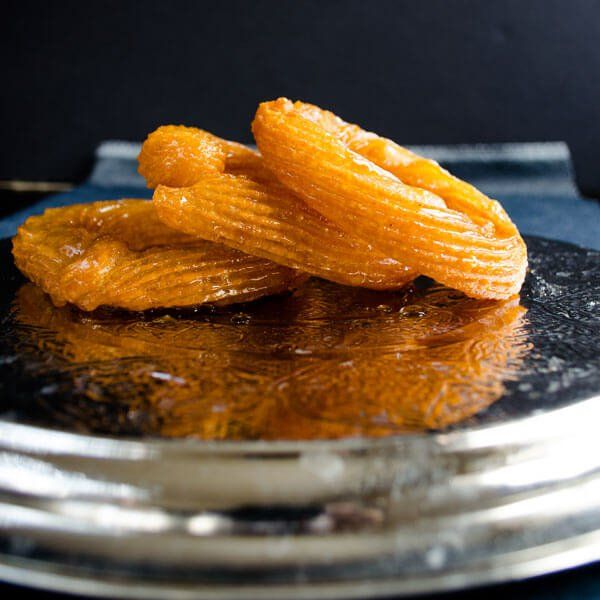 Turkish sweet churros aka Halka Tatlisi are one of the most loved street desserts in Turkey. It is fried dough dipped into sweet syrup.