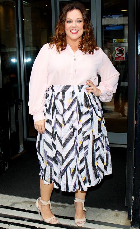 Melissa McCarthy in a pink house and patterned midi skirt