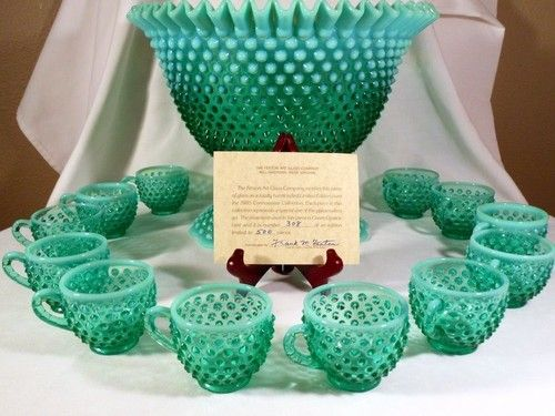14 Piece Fenton Green Opalescent Hobnail Punch Bowl Set.  Hobnail glassware gets its name from the studs, or round projections, on the surface of the glass. These studs were thought to resemble the impressions made by hobnails, a type of large-headed nail used in bootmaking.  Fenton Art Glass introduced Hobnail Glass in translucent colors in 1939 & Milk Glass Hobnail in 1950