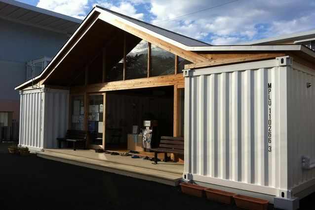Ban's community center is a large pitch-roofed space with amenities tucked into shipping containers. Image: Andrew Barrie