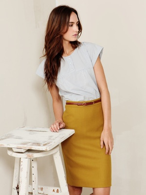 Thin belted mustard pencil skirt and angular sleeved blouse.