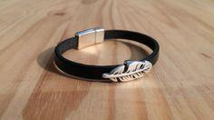 Bracelet de cuir noir réalisé à la main: -lanière de cuir noir de 5 mm de large -perle passante argentée «plume» -fermoir magnétique argenté Réalisé pour un petit garçon de …