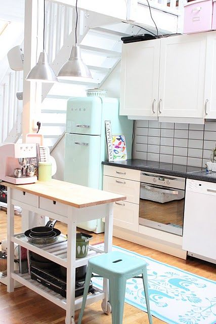 the ikea island cart painted white, with a turquoise stool sitting pretty next to it. Now I want one. Oh, and the retro fridge!