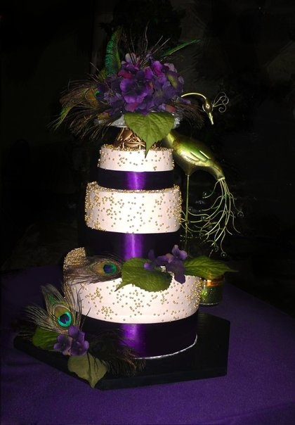 "This is awesome, but not in the price range I'm sure!....   Peacock Inspired Wedding Cake ~ colors: purple, green, teal, gold, champagne, three-tiers, thick 6 ½"" layers, champagne icing, gold dragees, dark purple ribbon, dark purple hydrangeas, and real peacock feathers."