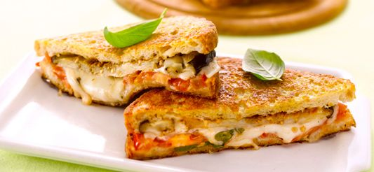 (voor 4 stuks)       Snij de mozzarella en tomaten in schijfjes.      Neem 4 sneetjes brood en beleg elk sneetje met gegrilde aubergines (ontdooid). Voeg de mozzarella toe, kruid met peper en zout en bedek met tomaten. Kruid opnieuw en doe er enkele basilicumblaadjes bij. Dek af met het resterende brood.      Klop de eieren los met de melk en de Parmezaanse kaas, kruid met peper en zout. Haal de boterhammen snel (aan beide kanten) door het eiermengsel.      Bak ze aan beide kanten goudbruin…