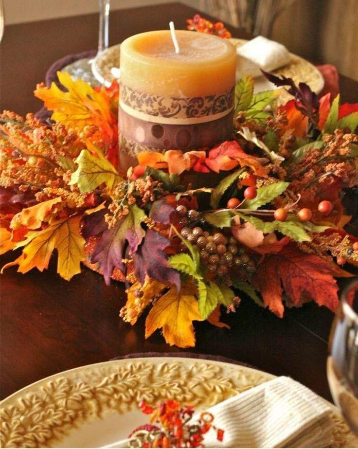 couronne de table composée de feuilles d'automne multicolores, baies rouges et une bougie cylindrique en marron
