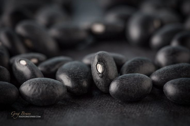 Black turtle beans on dark surface extreme closeup. Shallow depth of field.
