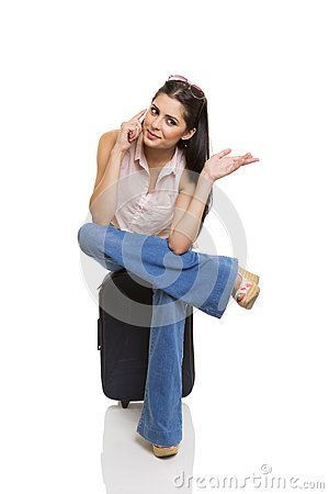 Pretty businesswoman sitting cross-legged on suitcase, talking to the cellphone and doing hand gesture.