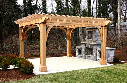 Outdoor Kitchen Pergola - This patio pergola, along with a very attractive outdoor kitchen, establishes an open-air room. Large paneled posts, with substantial beams and brackets, echo details of the home.