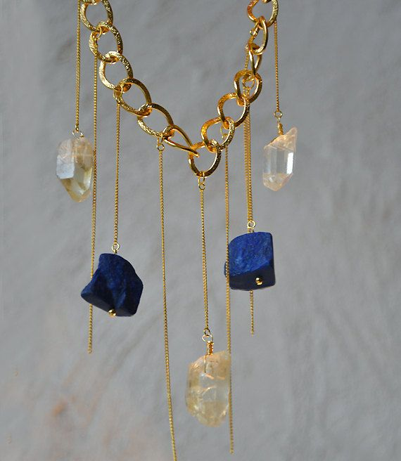 SOLD This is a unique gold plated necklace! It has a large chunky gold plated main chain and from there they are hanging  24k gold plated thin chains with two Afganistan, top grade, lapis lazuli large beads and three rock lemon quartz crystals at some of the ends! It closes with a  gold plated toggle clasp. You can wear it with any outfit! One of a kind piece made for one time only!