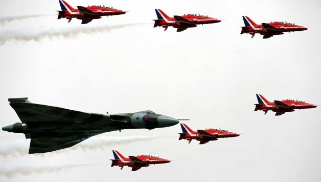 The Red Arrows fly in formation alongside a Vulcan bomber to officially open the Farnborough International Airshow in Hampshire, southern England, on July 9, 2012. Farnborough