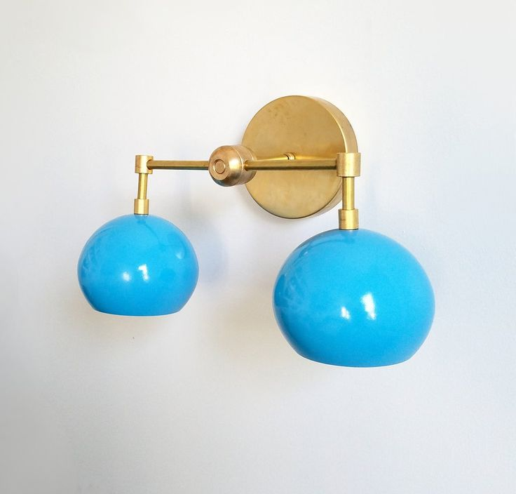 The Double Loa Sconce has a simple, minimalist design that can be fun or modern. Either way, it is bound to garner loads of compliments. This fixture is a two-light version of our single Loa sconce. The shades are globe-shaped and finished in a Mediterranean Blue Enamel. Measurements: width - approximately 16 inches height - approximately 9 inches depth - approximately 6 inches canopy = 5 inch diameter by 1 inch depth The light comes with all mounting hardware. It can be mounted in...