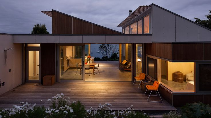 Architect Vaughn McQuarrie has replaced a 1920s cottage on New Zealand's Waiheke Island with a modest concrete and timber residence, set among mature gardens.
