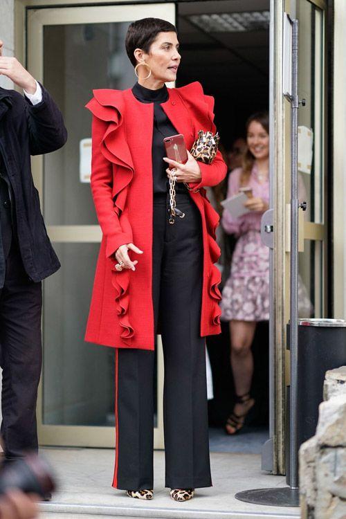 Девушка в удлиненном красном пиджаке с оборками и чемных брюках с лампасами