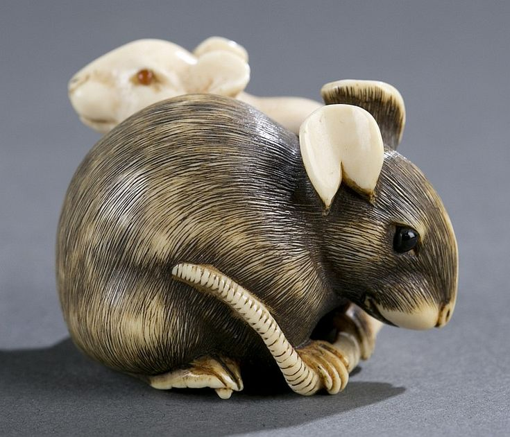 A Japanese ivory netsuke of two mice. Early 19th century. Larger mouse with carved black hair, nestled with smaller white mouse, both with inlaid eyes. Good carving to the hair and tail. Himotoshi on bottom, unsigned. 29.46mm