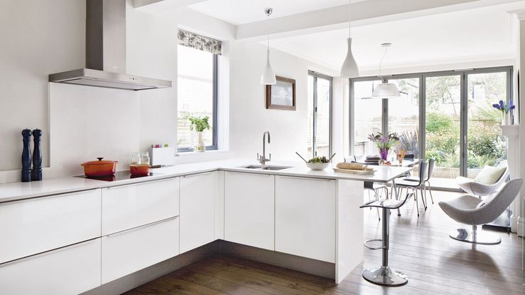 This contemporary kitchen-diner has the perfect open-plan layout for both entertaining and cooking. Crisp walls, sleek white units and inconspicuous handles fit the minimalist design with coherent fashion. The streamlined look is continued with icy quartz worktops and splashback.