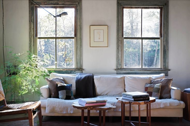 Nestled between two generous windows that catch the afternoon sun, a sofa with down-filled cushions, found in a shop nearby, features patchwork pillows.