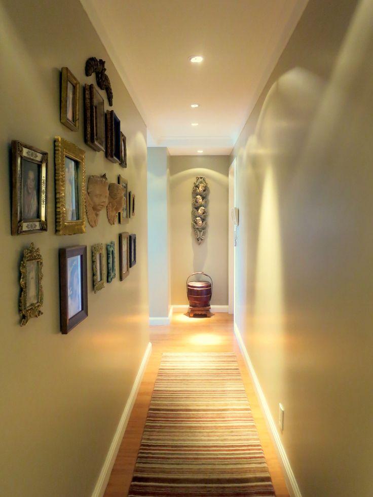 """Corredor estreito e longo vira galeria de fotos da família, com o uso de coleção de porta-retratos antigos. O tapete tipo passadeira com listras transversais também ajuda a """"alargar"""" o espaço."""