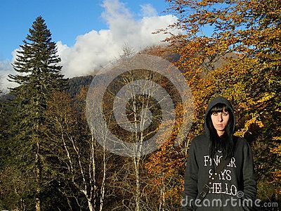 Girl on autumn walk in the mountains, beautiful nature, yellow leaves, fir trees, Krasnaya Polyana, Russia