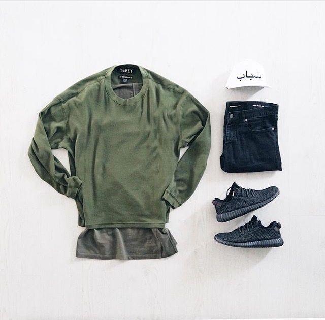 olive crewneck sweatshirt. long brownish greyish tee. dark blue denim. black / grey / charcoal sneakers. white hat.
