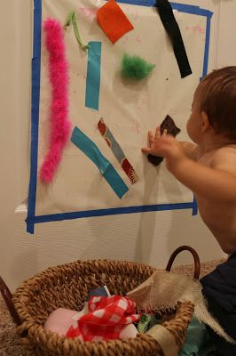 A fabric scraps treasure basket and a sticky wall - a perfect combination for sensory exploration.