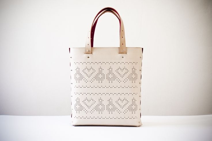 This beautiful leather bag comes with the typical bird motifs of Somogy and Sárköz regions of Hungary. The pattern is pierced into the leather by hand and the side detail gives a unique touch to the minimalistic shape.Measurements: 36 x 30 x 6 cm (height x width x depth)Colour: natural beige (gets darker over time), lining colour: redMaterial: vegetable tanned leather, woollen felt lining, metal accessoriesOther features: - zip closure - adjustable length shoul...