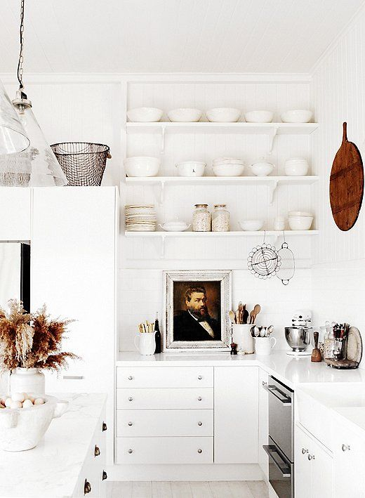 Love this all-white kitchen with open shelving and leather drawer pulls.