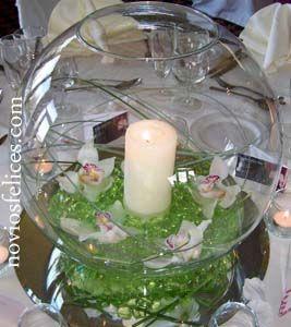 Original centro hecho con flores de orquídeas, vela central y perlas de agua en color verde