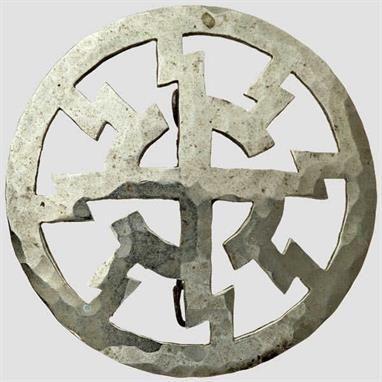 """Schmuckbrosche im Stil der """"Schwarzen Sonne"""" Gehämmertes Silber, Sonnenrad mit umlaufenden Sig-Runen, rückseitig angelötete Broschierung."""
