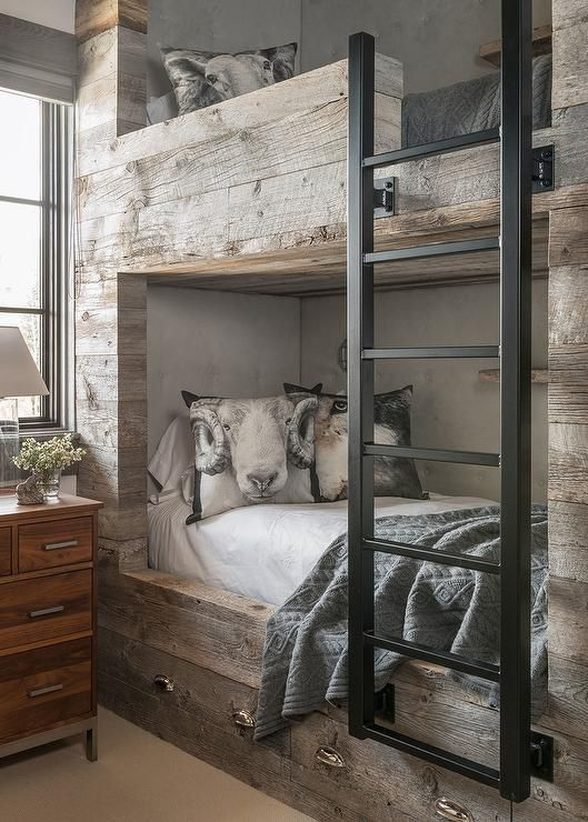 A wood dresser topped with a glass table lamp sits beneath a window dressed in a gray roman shade positioned beside rustic bunk beds fitted with an iron ladder and drawers adorning brass cup pulls and dressed in gray knitted throws accented with ram pillows.