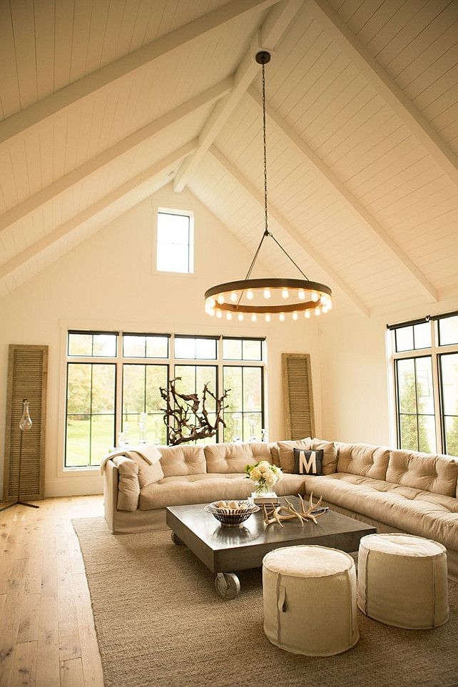 Lived-in family room with paneled cathedral ceilings,  Ralph Lauren Roark Modular Chandelier, beige tufted sectional, and a metal coffee table on wheels | Hahn Builders.