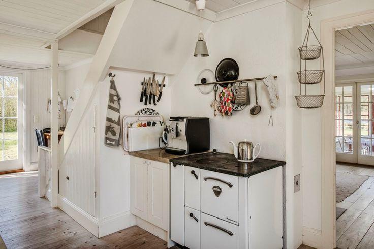 Köket med gammal vedspis och dörr till höger mot vardagsrummet