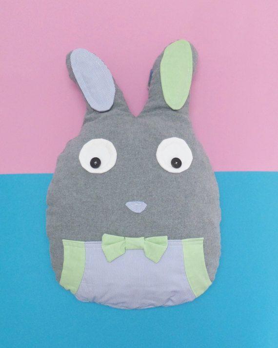 Conheça o nosso coelho, o Cenoura!  Almofada porta-pijama em forma de coelho. Com bolso na parte da frente e bolsa com fecho na parte de trás para guardar o pijama.  Utilização de tecidos cinzento escuro, azul às riscas e verde.  Muito fofo e ideal para bebés e crianças. Pode colocar no berço do seu bebé. O enchimento é de boa qualidade.  O tamanho deste modelo é de 60 cm de altura por 40 cm de largura.  Na opção em cima pode escolher entre olhos com botões ou em feltro preto.  Este produto…
