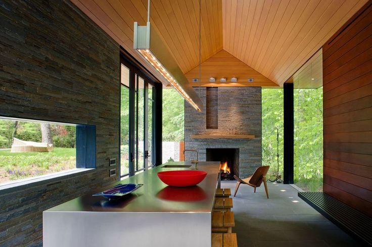 Cuisine ouverte, petite cheminée et des murs vitrés donnant sur le idyllique paysage extérieur