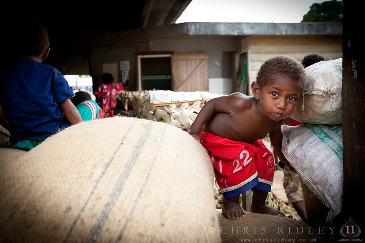 Little boy playing in the rice sacks at the market in Luganville, Santo Island, Vanuatu, South Pacific