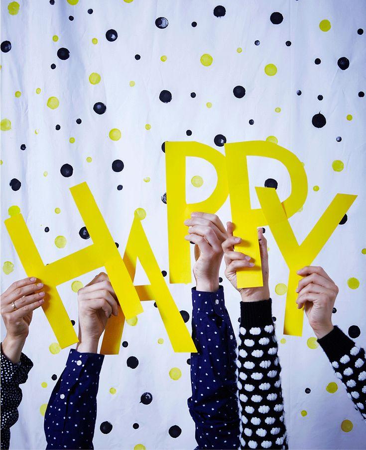 Papierbuchstaben und ein bunt beklebter Vorhang: mehr braucht es nicht für eine kreative Fotowand. Schlag deinen Gästen doch vor, sich passend zum Motto anzuziehen - wie hier im Pünktchenmuster.